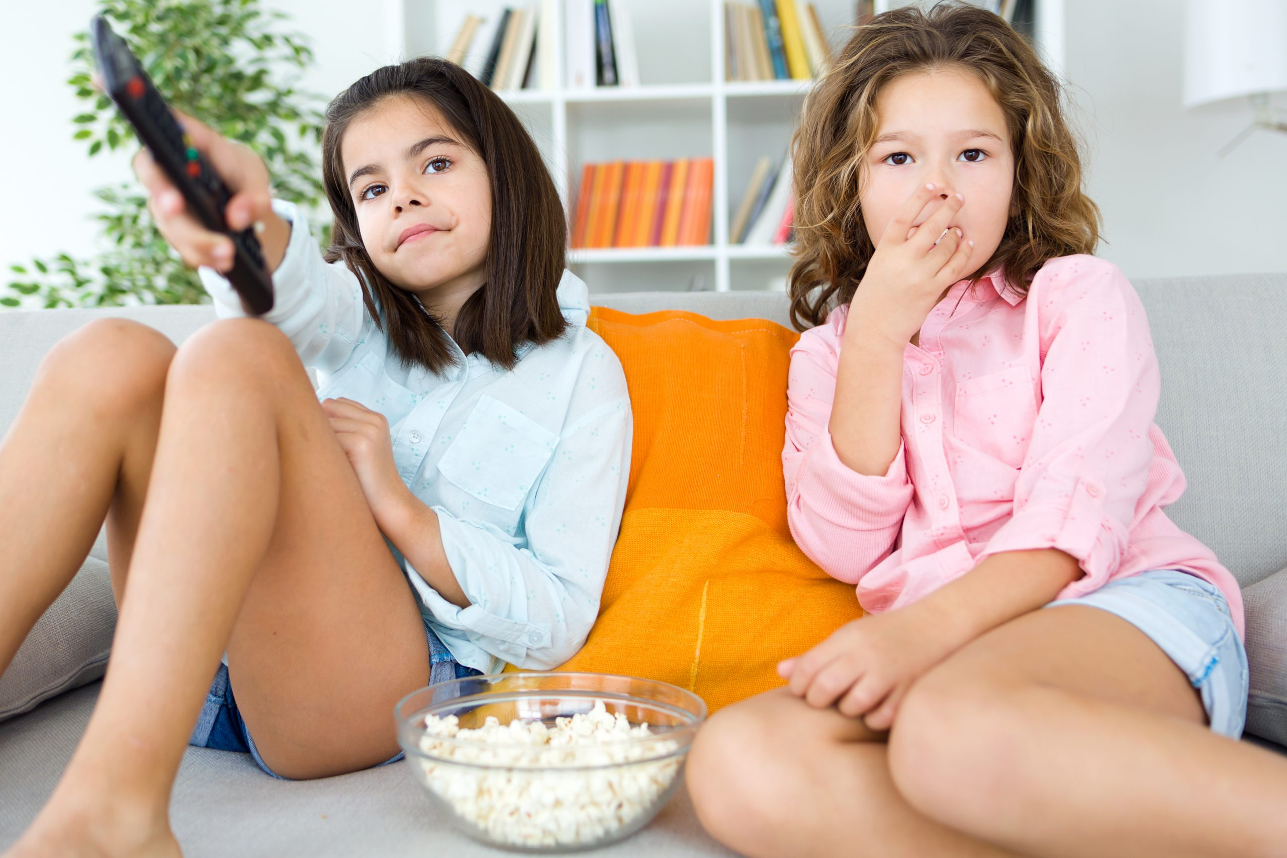 Portrait of beautiful young sisters eating popcorns at home.